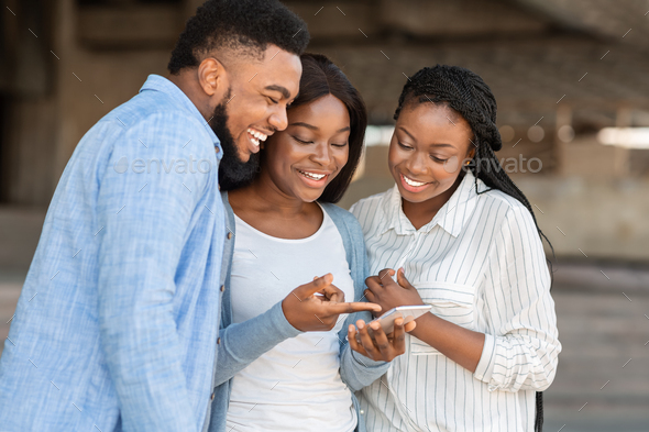 Cheerful african american friends watching funny videos on smartphone outdoors - Stock Photo - Images