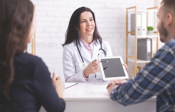 Doctor showing test results on digital tablet to married patients - Stock Photo - Images