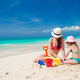Little cute girl and young mother building sandcastle at tropical beach - PhotoDune Item for Sale