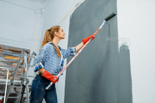 Female house painter in gloves paints the wall - Stock Photo - Images