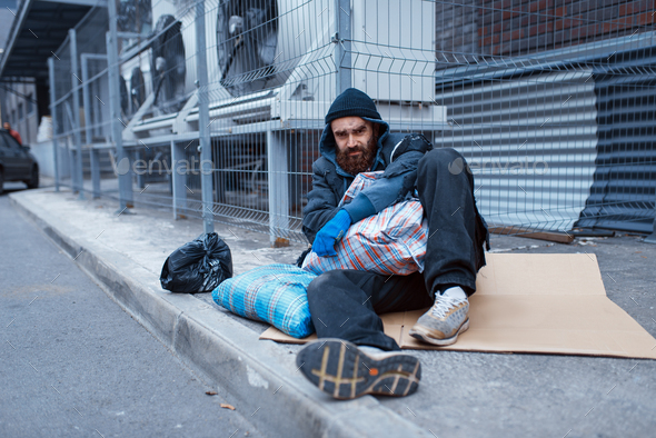 Male bearded beggar lies on city street - Stock Photo - Images