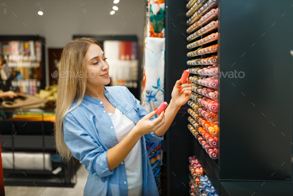 Seamstress buying threads in textile workshop - Stock Photo - Images