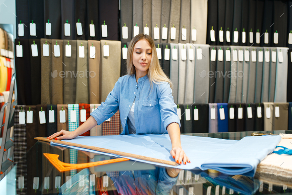 Woman measures the fabric in textile store - Stock Photo - Images