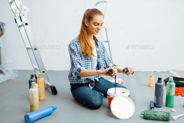 Female house painter mixes paints - Stock Photo - Images