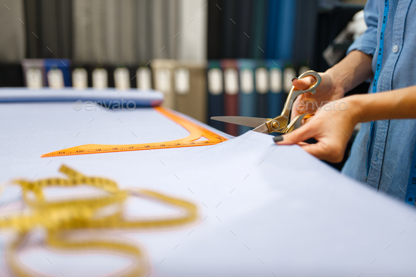 Seamstress cuts fabric with scissors in store - Stock Photo - Images