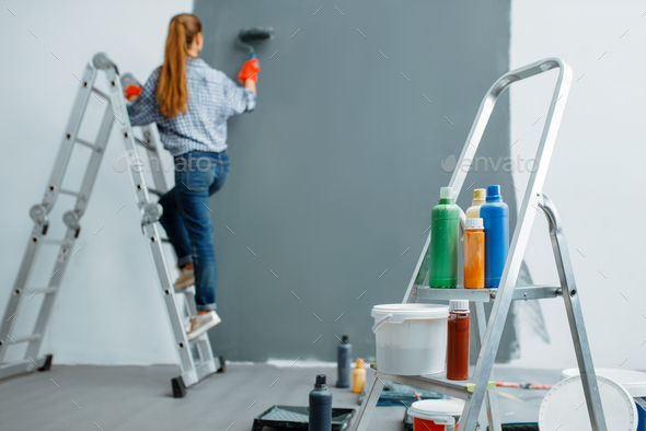 Female house painter paints walls indoor - Stock Photo - Images