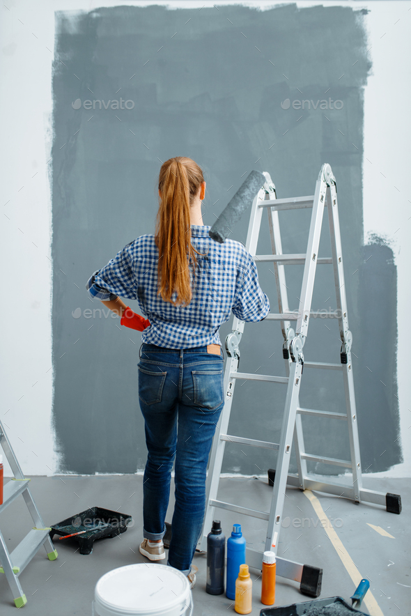 Female house painter looking on wall, back view - Stock Photo - Images