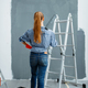 Female house painter looking on wall, back view - PhotoDune Item for Sale