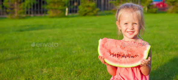 Little girl with big piece of watermelon in hands on green grass - Stock Photo - Images