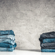 Stack of blue jeans on a gray background - PhotoDune Item for Sale