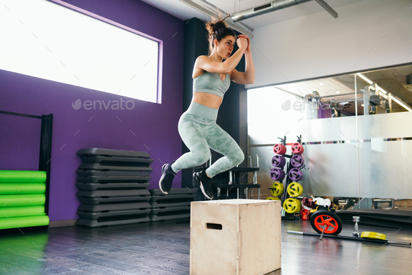 Fitness woman jumping onto a box as part of exercise routine - Stock Photo - Images