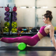 Woman relaxing her leg muscles with a green foam roller - PhotoDune Item for Sale