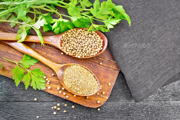 Coriander ground and seeds in two spoons on black board top - Stock Photo - Images