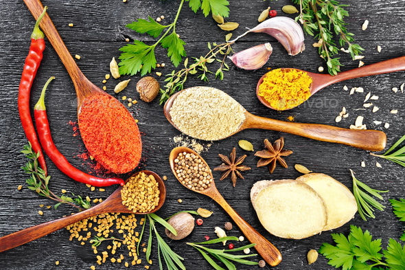 Spices in spoons on black board top - Stock Photo - Images