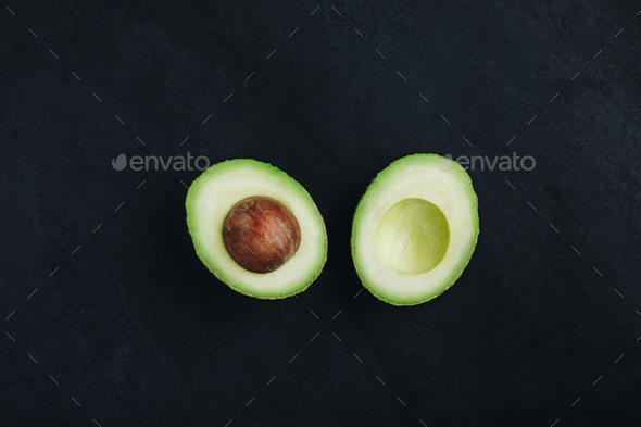 Raw avocado on dark stone background. Fresh green ripe avocado for guacamole. - Stock Photo - Images
