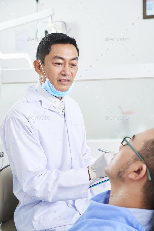 Mature Dentist Examining Patient - Stock Photo - Images