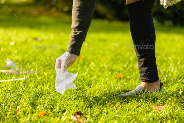Male volunteer picking up plastic from grass - Stock Photo - Images