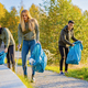Young volunteers picking up garbage in bag at park - PhotoDune Item for Sale