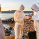 Young multi-ethnic scientists discussing water samples at beach - PhotoDune Item for Sale