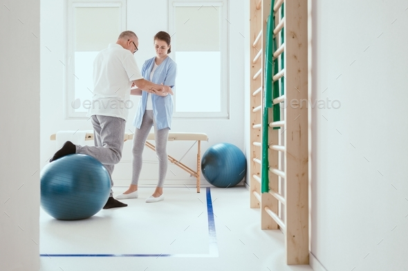 Young professional physiotherapist exercising with an injured patient using a blue ball - Stock Photo - Images