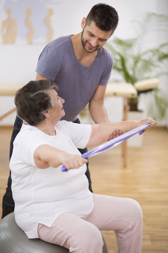 Elderly pensioner exercising with resistance bands with her professional physiotherapist - Stock Photo - Images