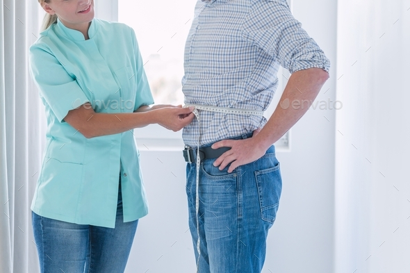 Young helpful dietitian measures the patient's waist circumference during the examination - Stock Photo - Images