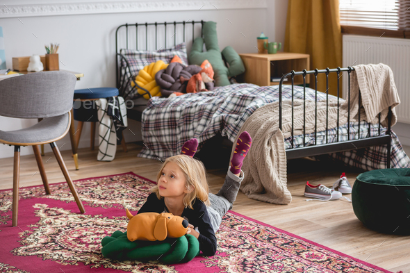 Cute blond girl on the floor of trendy child bedroom playing with her toys - Stock Photo - Images