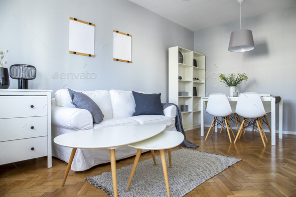 Stylish coffee table, comfortable sofa and dining room furniture in grey room - Stock Photo - Images