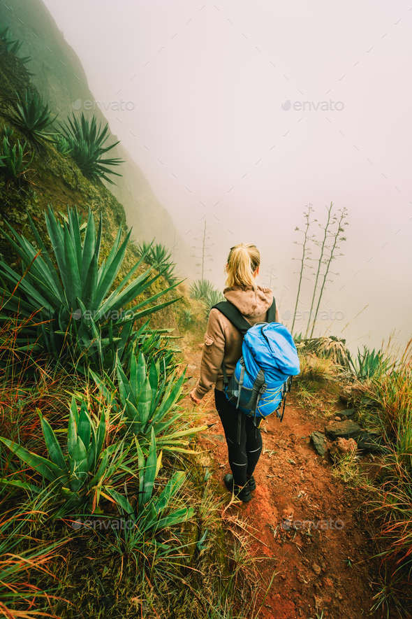 Santo Antao, Cape Verde. Women with backpack hike down the steep slope of the rock in the foggy - Stock Photo - Images