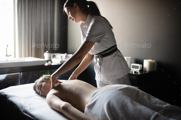 Masseur doing massage on female body in the spa salon. Beauty treatment concept - Stock Photo - Images