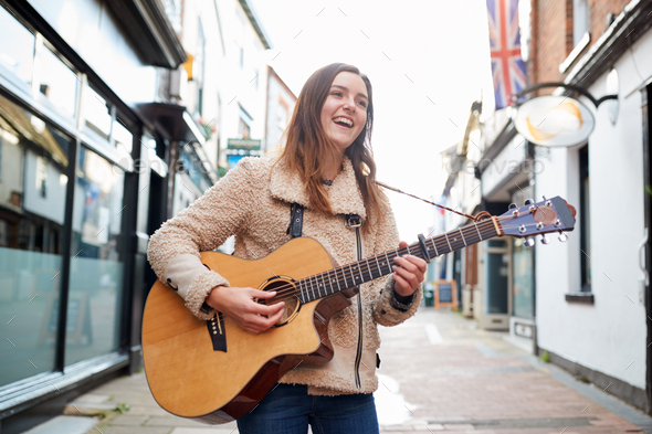 Female Musician Busking Playing Acoustic Guitar Outdoors In Street - Stock Photo - Images