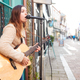 Female Musician Busking Playing Acoustic Guitar And Singing Outdoors In Street - PhotoDune Item for Sale