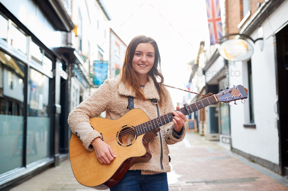 Portrait Of Young Female Musician Busking Playing Acoustic Guitar And Singing Outdoors In Street - Stock Photo - Images