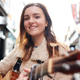 Portrait Of Young Female Musician Busking Playing Acoustic Guitar And Singing Outdoors In Street - PhotoDune Item for Sale