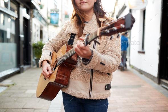 Close Up Of  Female Musician Busking Playing Acoustic Guitar  Outdoors In Street - Stock Photo - Images