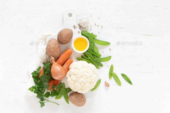 Fresh raw vegetables on white kitchen table, culinary background, top view - Stock Photo - Images