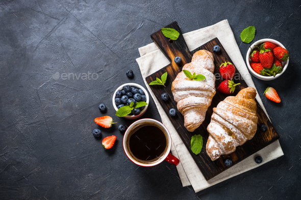 Croissant with fresh berries and cup of coffee on black - Stock Photo - Images