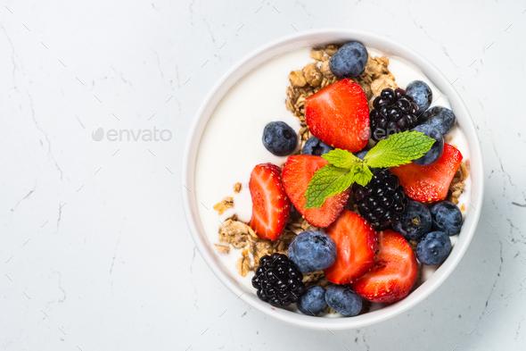 Greek yogurt granola with fresh berries on white table - Stock Photo - Images