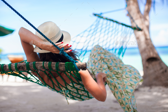 Rear view of Young woman enjoying a sunny day in the hammock - Stock Photo - Images