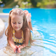 Closeup of Cute little girl in the swimming pool looks at camera - PhotoDune Item for Sale