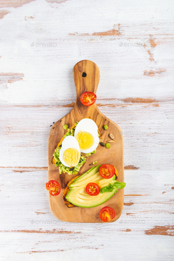 Sweet potato toasts with avocado, eggs, tomatoes and sesame seeds - Stock Photo - Images