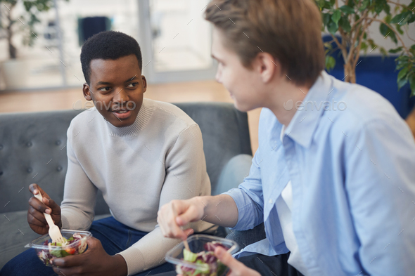 Young Men Enjoying Lunch in Office - Stock Photo - Images