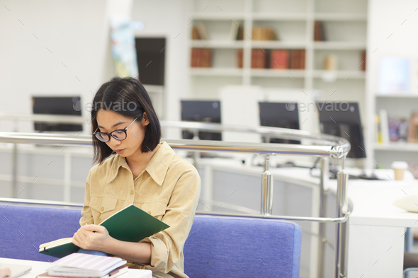Young Asian Woman Reading in Library - Stock Photo - Images