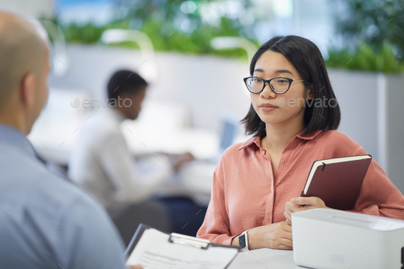 Asian Woman Talking to Manager at Work - Stock Photo - Images
