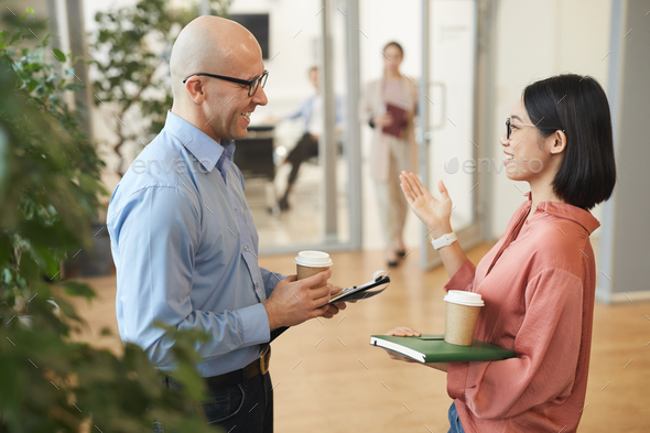 Asian Young Woman Chatting with Colleague at Work - Stock Photo - Images
