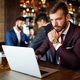 Portrait of a successful business man sitting at the cafe working on a laptop - PhotoDune Item for Sale