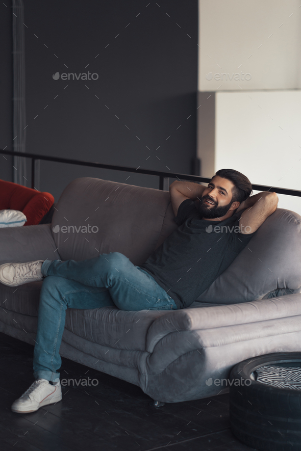 Young man sitting relaxing on the couch - Stock Photo - Images