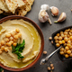 Hummus topped with chickpeas, sun dried tomatoes and green coriander leaves on stone table - PhotoDune Item for Sale