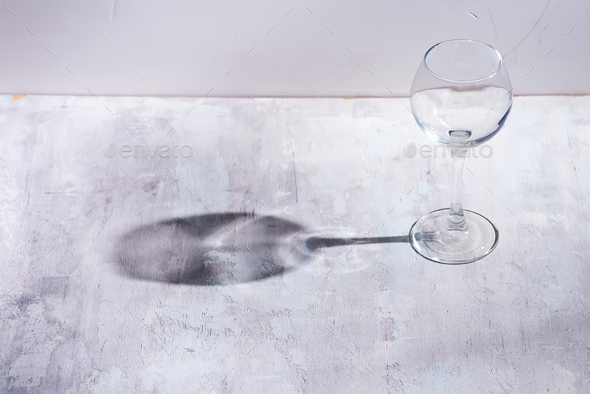 Wine glass with sun hard light shadow reflection on stone background - Stock Photo - Images