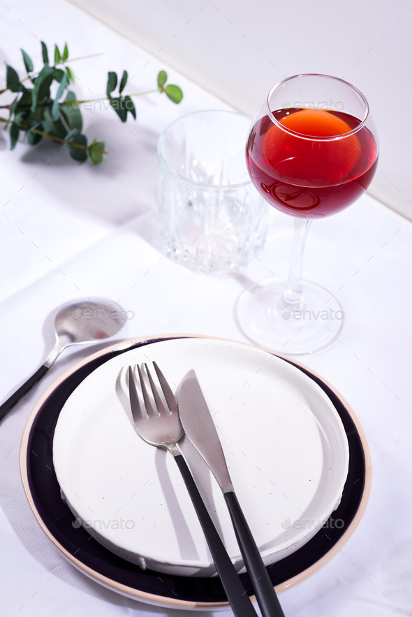 Tableware and decorations for serving a festive table. Plates, red wine glass and cutlery with green - Stock Photo - Images